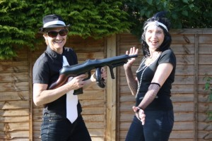 Gangster – hat, pencil moustache, white tie, inflatable gun(strapped on your back) Glamorous Moll – black wig, beads, net gloves, hair band.